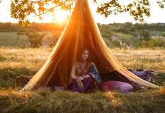 Luxurious Indian girl is sitting in a tent outdoors, at sunset. royalty free stock photography