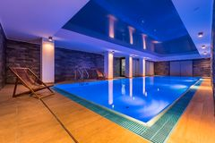 Luxurious indoor swimming pool. And stylish, wooden deckchairs stock photography