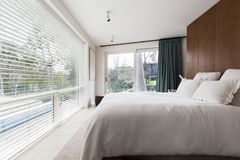 Luxurious interior designed bedroom with amazing view of the poo. L and trees royalty free stock photography