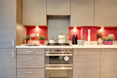 Luxurious kitchen. Frontal image of brightly coloured luxurious modern kitchen with pans, utensils and ingredients on the worktop royalty free stock image