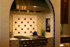 Luxurious kitchen range. Luxurious stainless steel kitchen range in alcove decorated with blue and white ceramic tiles royalty free stock photos