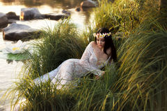 Luxurious lady, in elegant long dress lying on shore of lake Royalty Free Stock Photos
