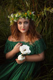 Luxurious lady in long green dress with bare shoulders. Royalty Free Stock Image