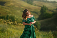 Luxurious lady in long green dress with bare shoulders. Stock Photography