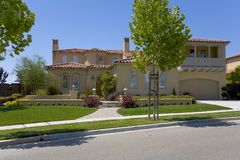 Luxurious and Large Custom Home. Exterior shot of a large, luxurious custom home that features a stucco exterior and a balcony Royalty Free Stock Photography