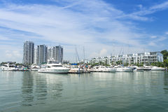 Luxurious Living. Docking of pleasure luxurious yacht at marina against modern residential building royalty free stock photos