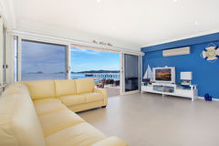 Luxurious living room. Luxurious, spacious apartment living room with waterfront visible through sliding doors Royalty Free Stock Images