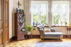 A luxurious living room interior with a couch and a wooden cabin. Et standing on a parquet against two large windows. Real photo. concept stock images