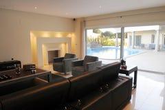 Modern Living Room, Lighted Fireplace, Blue Pool, Luxury Stock Image