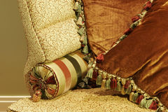 Luxurious Love Seat with Pillows. Close up of love seat with satin and velvet pillows trimmed with tassels and piping stock photo