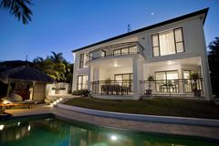 Luxurious mansion exterior at dusk overlooking poo Stock Photos