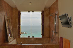 Luxurious marble bath tub. With ocean view and flat screen TV royalty free stock photography