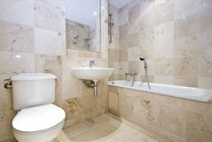 Luxurious marble bathroom. With a large classy bath, wash basin and toilet Stock Photography