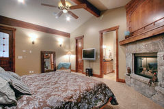 Luxurious master bedroom. Interior of luxurious master bedroom with fireplace and ceiling fan royalty free stock image