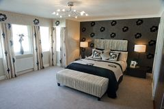 Luxurious master bedroom. Interior details of luxurious modern master bedroom with tasteful decoration Stock Images
