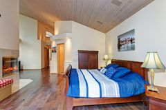 Luxurious master bedroom with vaulted ceiling. Over a wooden sleigh bed facing a double sided fireplace royalty free stock photos