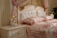 Luxurious modern bedroom. Interior details of luxurious modern bedroom with pink duvet cover and stylish headboard Stock Photos