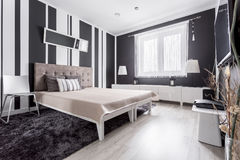 Luxurious modern bedroom. With striped wallpaper and bed with headboard stock photos