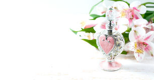 Luxurious perfume bottle with flowers on white background. Feminine beauty concept. Stock Photo