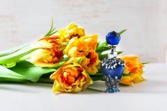 Luxurious perfume bottle with flowers on white background. Feminine beauty concept. Royalty Free Stock Image
