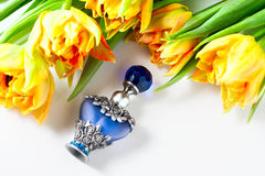 Luxurious perfume bottle with flowers on white background. Feminine beauty concept. Stock Image