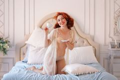 A luxurious pin up lady dressed in a beige vintage lingerie posing in her bedroom and have a cup of breakfast tea. Pretty cute joyful lady wearing vintage stock photos
