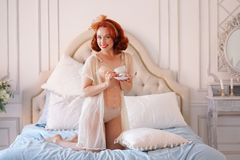 A luxurious pin up lady dressed in a beige vintage lingerie posing in her bedroom and have a cup of breakfast tea. Pretty cute joyful lady wearing vintage royalty free stock photo