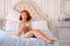 A luxurious pin up lady dressed in a beige vintage lingerie posing in her bedroom and have a cup of breakfast tea. Pretty cute joyful lady wearing vintage stock photography