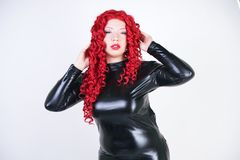 Luxurious plus size woman with Asian face, bright makeup and red curly hair posing in shiny closed long black dress on white backg. Round in Studio. hot adult stock photo