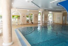 Luxurious pool interior design, sunlight from panoramic Windows, stylish columns and turquoise water.  stock photo