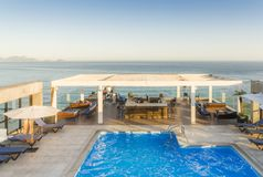 Luxurious pool and lounge on rooftop overlooking the ocean. Luxurious pool and lounge area with bar overlooking a tropical ocean during golden hour - captured in royalty free stock photography