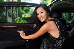 Luxurious portrait. Portrait of a young woman dressed for a party sitting in a luxurious car royalty free stock photography