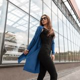 Luxurious pretty young hipster woman in fashionable clothes in sunglasses on a warm summer day walks along a city street. Near a modern glass building stock photography