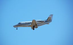 Luxurious private jet approaching airport. Charter jet airplane for corporate and business travel stock photography