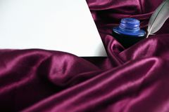 Quill on purple silk satin with ink and white paper stock photos