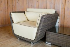 Luxurious rattan wicker armchair next to coffee table. Interior decoration pattern stock image