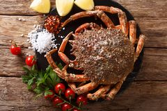 Luxurious Raw spider crab surrounded by fresh tomatoes, lemon, h. Erbs and spices close-up on a black stone. Horizontal top view from above stock photo