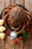 Luxurious Raw spider crab surrounded by fresh tomatoes, lemon, h. Erbs and spices close-up on a black stone. Vertical top view from above royalty free stock images