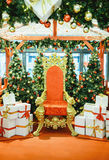 Luxurious red chair Santa Claus throne and gifts Royalty Free Stock Photography