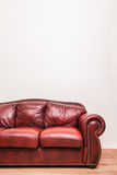Luxurious Red Leather Couch in front of a blank wall. To ad your text, logo, images, etc Royalty Free Stock Photo