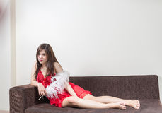 Luxurious redhead woman in a red dress on brown couch. Asian girl sexy wearing red dress on the sofa Royalty Free Stock Photos