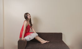 Luxurious redhead woman in a red dress on brown couch Royalty Free Stock Photos