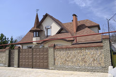 Luxurious residential building. The chic residential house behind the fence Stock Photography