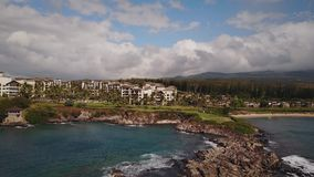 Beautiful aerial panorama of most expensive resort montage kapalua and bursting waves of ocean on island maui,hawaii stock footage