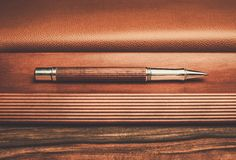 Luxurious rollerball pen. On a wooden background Royalty Free Stock Photo