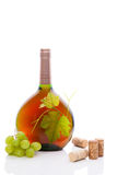 Luxurious rose wine still life. Luxurious rose in green round bottle without label with green wine grapes and grape leaves and various wine corks on white Royalty Free Stock Image