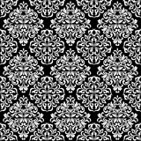 Luxurious seamless pattern. White ornate Damask ornament on a black background. Elegant tracery from swirls and foliage. Ideal for textile print and wallpapers Royalty Free Stock Images
