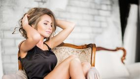 Luxurious sensual bloonde woman in lingerie sitting on couch Stock Photos