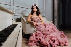 Luxurious girl in an evening cloudy dress sitting on a sofa in the studio interior. royalty free stock photos