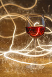 Luxurious shot of rose wine glass on gold glitter Royalty Free Stock Images